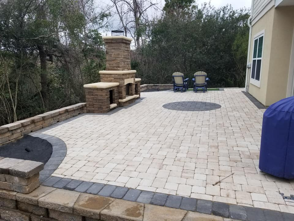 Look at this beautiful paver patio and outdoor fireplace with log storage